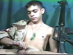 Young soldier with a gun having fun while stroking his dick